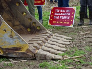 A protest sign rests on the ground next to the bucket of a backhoe.