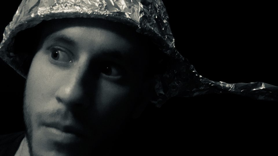 crazed person wearing tin foil hat