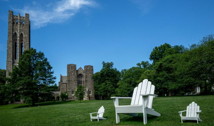 "A view of Clothier Hall across Parrish Beach with three Adirondack chairs visible, one of them being the ""Big Chair"" built by Jake Beckman '04"
