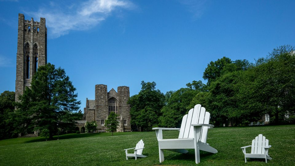 """A view of Clothier Hall across Parrish Beach with three Adirondack chairs visible, one of them being the """"Big Chair"""" built by Jake Beckman '04"""