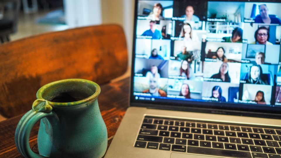 laptop showing many people in small windows on a zoom call with a blue coffe mug to the left