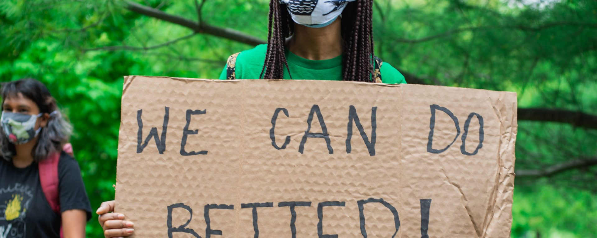 """A masked protester holding a cardboard sign which reads """"We can do better!"""" Photo taken by Jason Hargrove"""