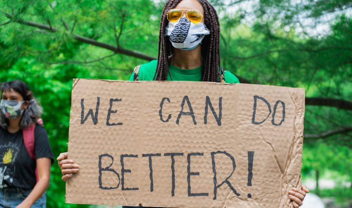 "A masked protester holding a cardboard sign which reads ""We can do better!"" Photo taken by Jason Hargrove"