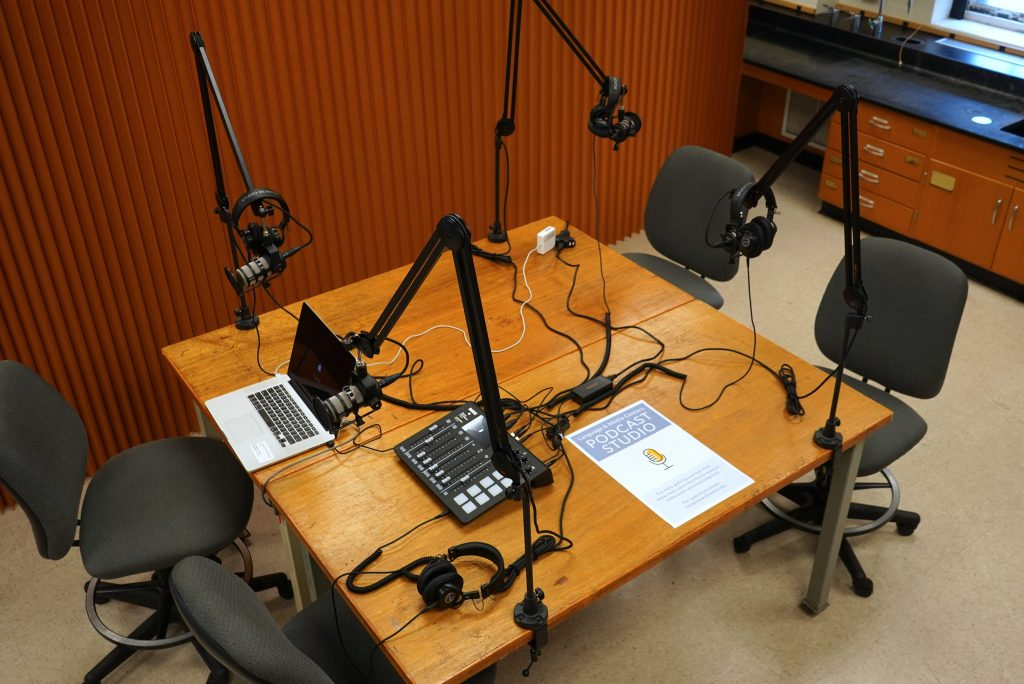 """A brown table with 4 microphones and headphones on articulating arms, a laptop and audio mixer sit on the table. A display sign announces """"Podcast Studio""""."""
